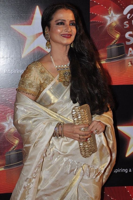 Rekha wearing off white silk saree with white and gold shades. The saree is paired with half sleeves gold colour blouse and pearls necklace