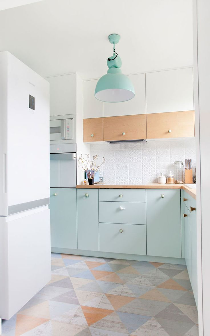The pastel blue used on the lower cabinets of this small kitchen compliment the other other pastel colors used on the floor and works with the light wood countertops and partially wood upper cabinets.