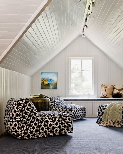 Fun attic lounge room with painted tongue and groove clad walls and ceilings over a built-in window seat accented with anchor print pillows with Links Bean Bag Chair Loungers in front atop a denim blue colored rug.