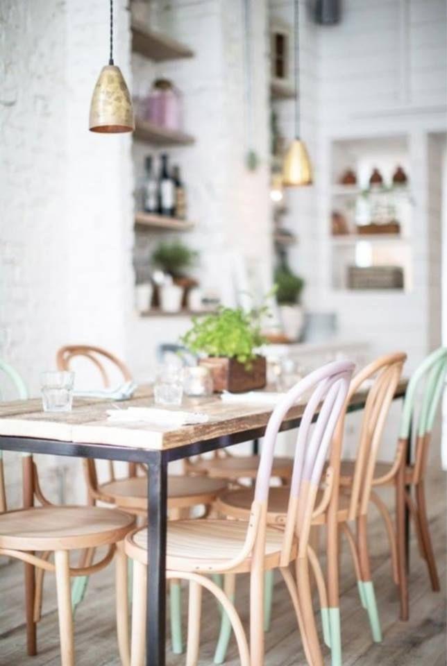 Fraaie combi van witten met een lichte houten vloer, cafe stoelen en tafel met pastel en metallic accenten .