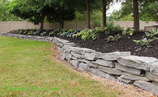 Build A Stacked Stone Garden Wall Stone Landscaping Stacked Stone Walls Stone Walls Garden