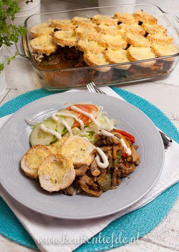 Shoarma-ovenschotel: gebakken shoarmavlees, uien, paprika's, champignons, stokbrood, kruidenboter en kaas, kort gegratineerd in de oven