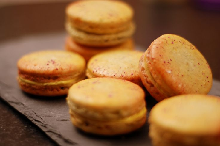 Handpainted Saffron-Orange Blossom macarons on Orange-Pistachio shells.