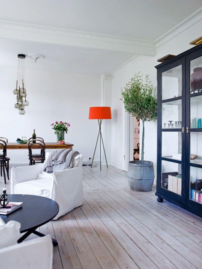 In 't oog        Dit beeld heeft de volgende tags:   bank huiskamer kast lamp plant rood tafel   De rode lamp in de hoek van de kamer springt direct in het oog. Het kan heel spannend zijn om met felle kleuren te werken in een basic witte woonkamer. Het voorkomt dat je interieur braaf oogt. Fotografie Birgitta Wolfgang Drejer/ Sisters Agency.
