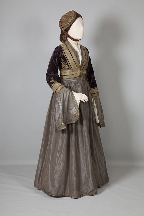 'Amalia' costume Athens, Attica. Late 19th c. © Peloponnesian Folklore Foundation. The urban costume of the Peloponnese spread to other parts of Greece after 1837, when Amalia, the first Queen of Greece, adopted it as the official court dress, combining the Biedermeier style with the local kavádi and zipoúni. The dress is made of taffeta, with an open bodice to show the neck opening of the chemise. The kondogoúni is of velvet, gold-embroidered and very close-fitting. The cap is a kalpak.