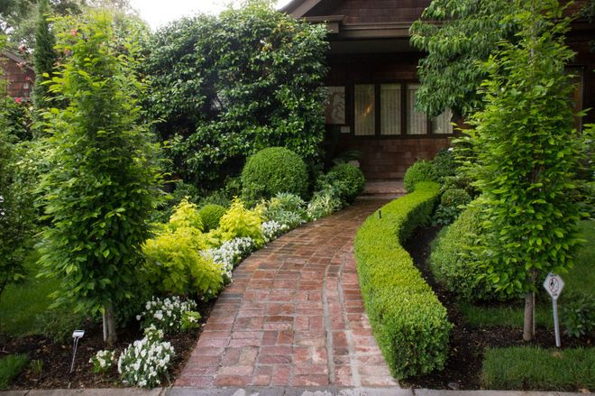traditional landscape by Hoi Ning Wong~ A low boxwood hedge on one side of the brick entry path creates balance but isn't symmetrical. This use of traditional garden elements in a modern way carries through the rest of the design.