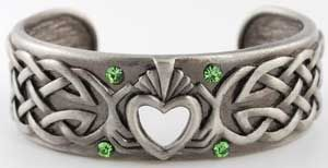 "Celtic Claddagh Bracelet A potent symbol of everlasting love, this bracelet displays the Celtic symbol of the Claddagh, or two hands coming together to hold up a bracelet. Made of pewter, this is a solid bracelet with an open back. 2 1/2"" wide, face is 3/4"" across at widest point."