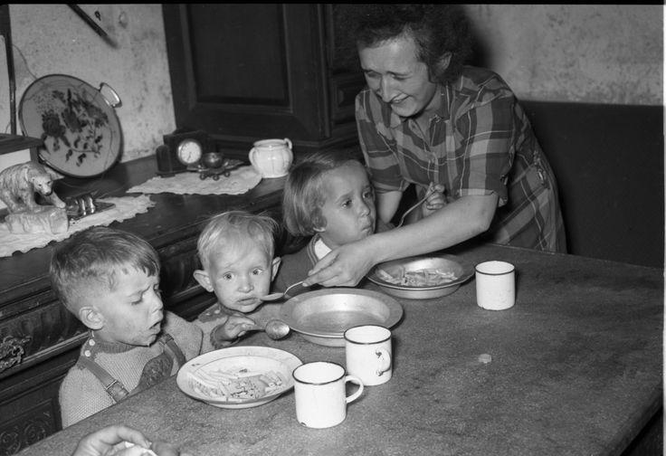 """Kinder im Schönau-Bunker in einer Wohnzelle beim Essen. Die Inszenierung für das Foto, der """"gutbürgerliche"""" Schrank im Hintergrund und die """"Sonntagskleidung"""" täuschen über die tatsächliche Not der Bunkerbewohner hinweg. Foto: StadtA MA - ISG"""