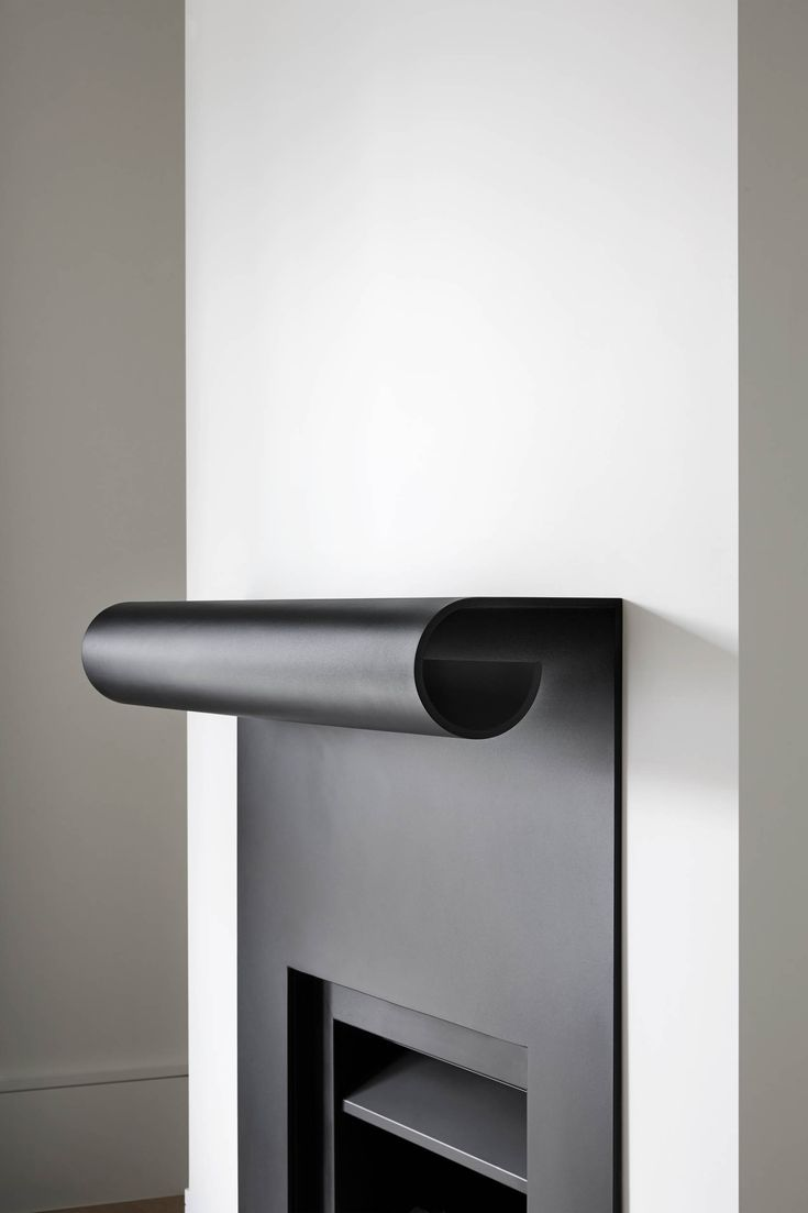 Curved black steel fireplace mantle at Winter Street Residence
