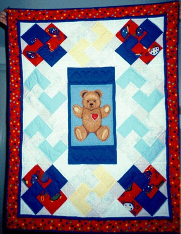 """""""Teddy Bear surrounded by Card Tricks"""" (December 1994, Davis, CA) - Made for my first niece, Clarissa, for her first Christmas.  I enjoyed making my first """"kid quilt"""" and really enjoyed how the borders and quilting turned out.  The center is a teddy bear that was given to me by my mother from her collection. I surrounded it with the different colored """"Card Tricks"""" blocks. I still have pictures of a baby Clarissa sitting on her quilt looking so sweet. Machine pieced, hand quilted."""