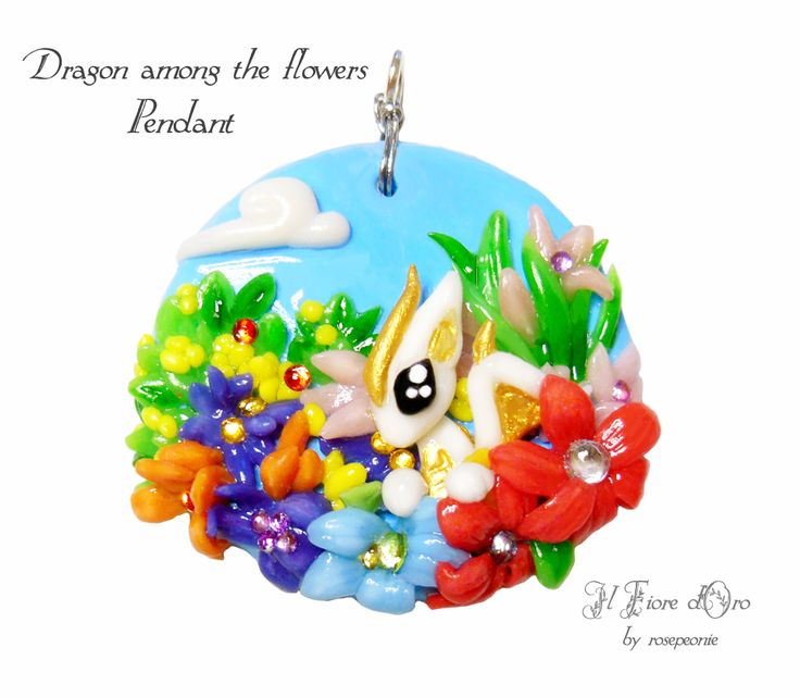 """Dragon among the flowers"", pendant with a little white dragon peeking out from a colourful bush of leaves and flowers (daisies, irises and much more).  Made in low relief, entirely by hand from molding to painting. Among the flowers many coloured rhinestones shine, catching the light and giving..."