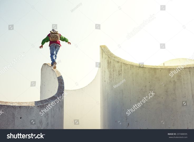 brave extreme man with backpack walking on a thin concrete wall