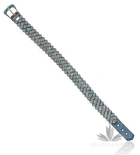 Bransoletka srebrna w kolorze rose gold - miedziane złoto. Wysadzana drobnymi, turkusowymi kamyczkami fasetowanymi. Długość bransoletki to 18-20 cm - możliwa regulacja na przepięknym, ozdobnym zapięciu w kształcie paska z klamrą. Szerokość wzoru to około 1,2. Całość wykonana ze srebra próby 925, z dbałością o najmniejsze detale.