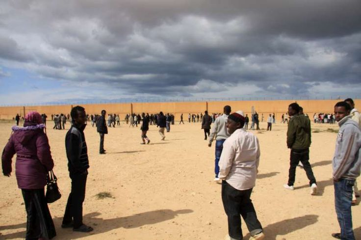 Men from sub-Saharan Africa, including Somalis and Eritreans, mill in the vast yard of a detention centre in Benghazi. ©UNHCR/L.Dobbs