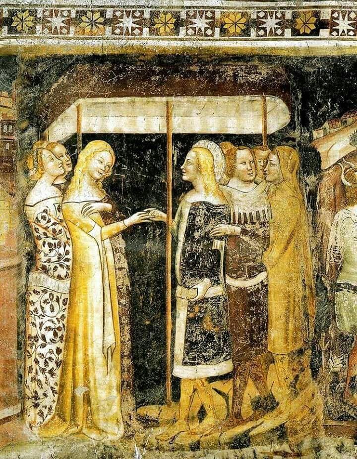 """affresco del duomo di Trento , di Mons de Bononia, del 1347 c., raffigurante (sotto il baldacchino rituale) s.Giuliano vestito con gonnella scura foderata di pelliccia (a destra) che infila l'anello alla sposa vestita di gonnella (tunica) dorata, sopra cui indossa la sopravveste con maniche tagliate al gomito ( da cui scendono lunghi """"batoli"""") bipartita in tessuto dorato e di porpora.Vedi che i capelli sono lunghi come quelli della sposa (mentre le altre giovani li tengono raccolti in…"""