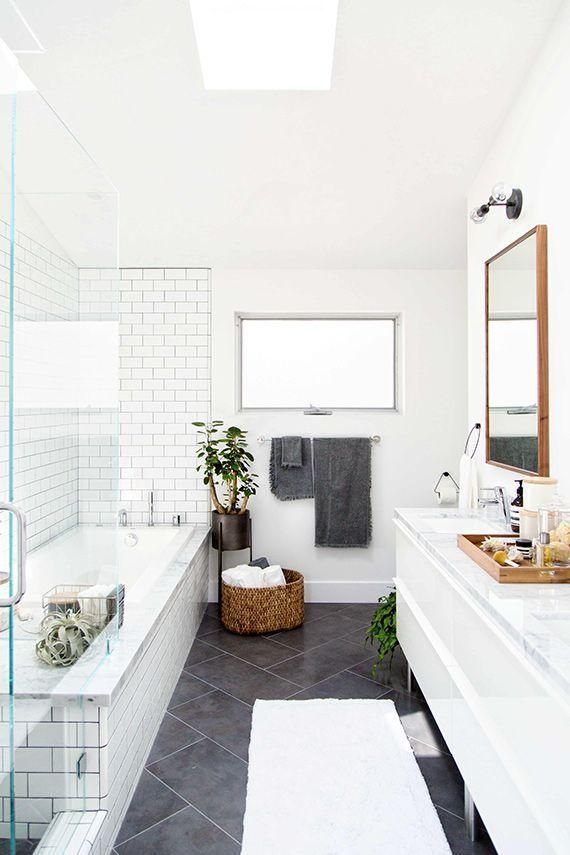 Classic but modern gray and white master bathroom design with wide herringbone chevron floor tiles, brick pattern white subway tiles with gray grout in the shower, white lacquer credenza under the basin sink, blackened bronze wall mounted sconce, vibrant green potted plants, and warm wood accents from the vanity tray, towel basket and rectangular vanity mirror.