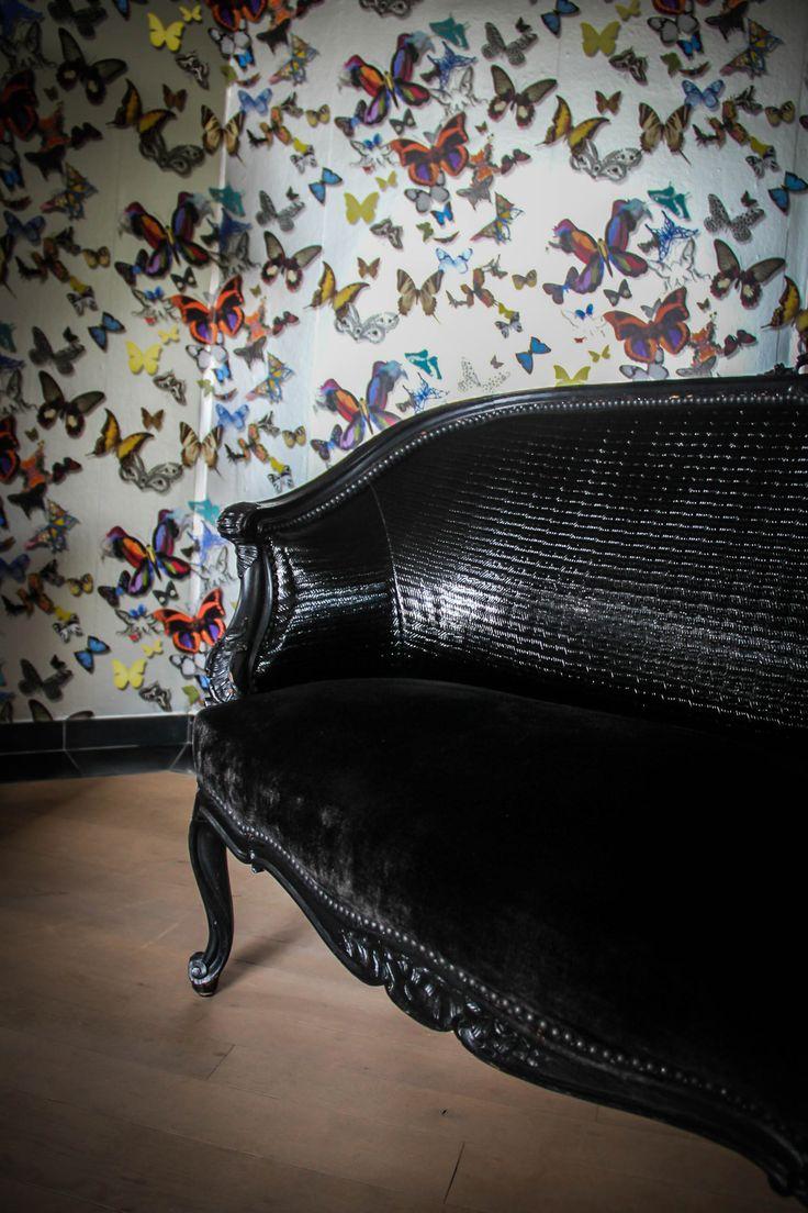 """Fauteuil d'époque recouvert de différents tissus noirs, tapisserie """"papillons"""" colorés."""