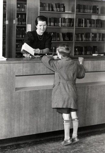 In de rooms-katholieke openbare leeszaal staat een jongen aan de balie, terwijl de bibliotheekmedewerkster hem een boek laat zien, Breda, Nederland, 1939.