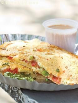 An uttapa with a difference! the spread-out batter is topped with veggies and coated with another layer of batter, to make a sandwich, which is then cut into equal wedges and served hot with the typical south indian accompaniments -- Tarla Dalal