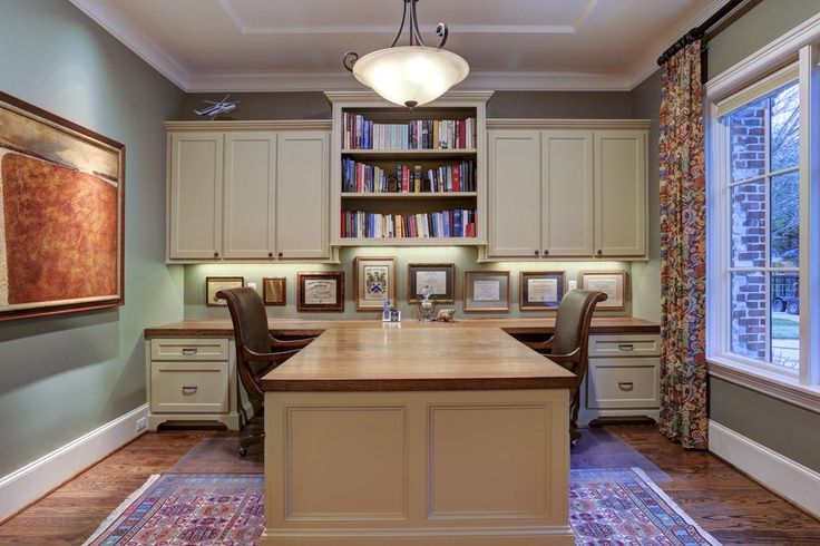 3506 Suffolk Dr, Houston, TX: Photo Just off the entry is the study. A built-in bookshelf flanked with cabinets hang above a custom, built-in partners desk that can be disconnected in order to move or change the area rug.