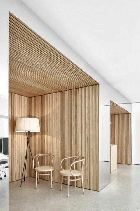 Recepción y sala de espera para oficinas o centros de salud. Pared-espejo, laminado de madera, suelo de hormigón pulido