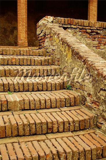 Old brick stairs and columns in Tuscany with moss