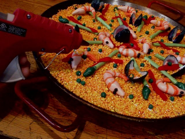 Fake Paella for 4. You'll need bomba rice, assorted acrylic paint, glue gun, air dry clay, multi-purpose glue, gloss glaze spray, felt    Mix rice with red & yellow paint, let dry. Make seafood, peas and asparagus with clay. Let them dry then paint. Cover a paella pan with glue and sprinkle the rice on it. Decorate with clay pieces, cut strips of red felt and decorate the dish with handmade PIQUILLO PEPPER STRIPS :D Spray Triple thick brilliant gloss glaze. Fool your in~laws on their next…