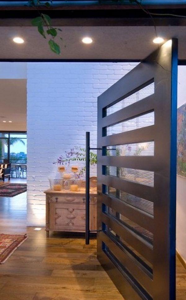An elegant wooden pivot door design with glass details