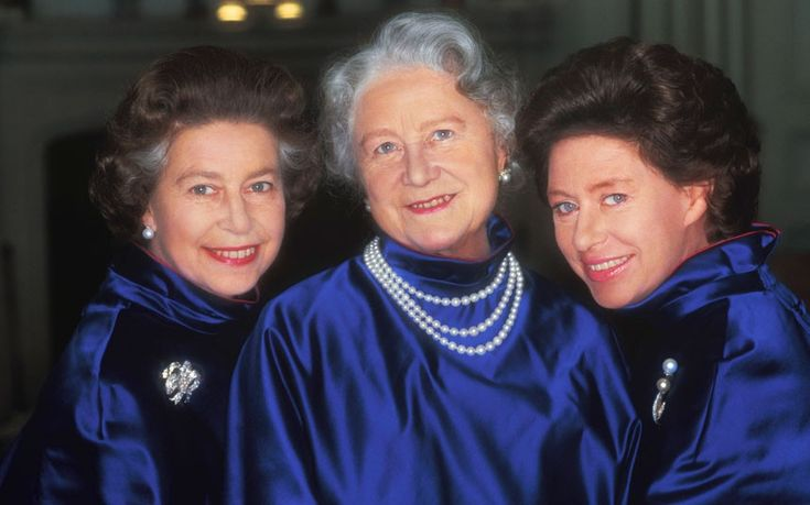 Her Majesty Queen Elizabeth II, Her Majesty Queen Elizabeth the Queen Mother, and Her Royal Highness Princess Margaret wear matching blue satin jackets for an official portrait by Norman Parkinson
