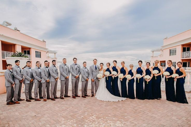 Outdoor Rooftop Wedding Party Portrait, Bridesmaids in Halter Navy Blue Column Lulu's Zenith Dresses, Bride in Lace Cap Sleeve A Line Sincerity Bridal Wedding Dress, with White Floral Bouquet, and Groomsmen in Light Gray Suits with Blue Bowties and Brown Shoes | Tampa Bay Wedding Photography Rad Red Creative | Waterfront Hotel Wedding Venue Hyatt Regency Clearwater Beach #outdoorweddingphotography #redweddingdresses