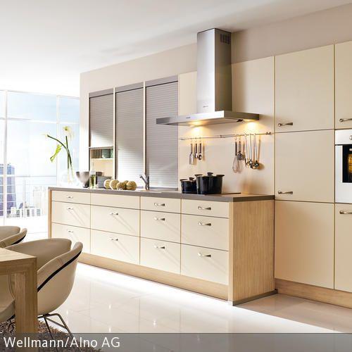 Die beigefarbene Küchenzeile wirkt freundlich und harmoniert mit dem hellen Holz des Esstischs. Der glatte, weiße Boden ermöglicht effiziente Reinigung nach jedem …