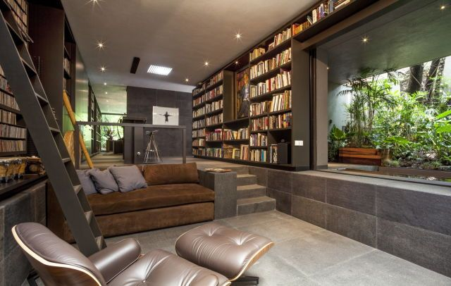 Sunken living room surrounded by bookshelves with an open view of the garden, Mexico City, Mexico [2000×1269]