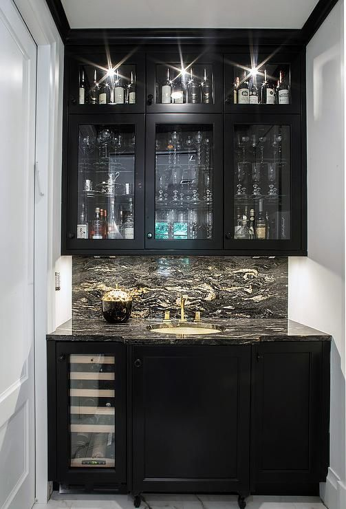 Chic black wet bar boasts white walls lined with black crown molding complementing black cabinets fitted with a built in glass front wine fridge and a black and white marble countertop holding an round undermount sink with a brass faucet in front of a black and white marble backsplash lit by custom lighting fixed beneath glass front upper cabinets.