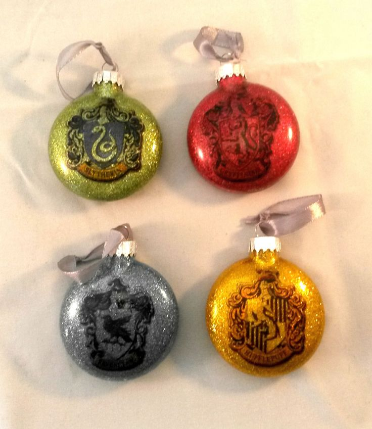 Set of 4 Harry Potter themed baubles which include one gold glitter bauble with Hufflepuff symbol, one light green glitter bauble with Slytherin symbol, one light blue glitter bauble with Ravenclaw symbol and one red glitter bauble with the Gryffindor symbol. Each bauble is made out of glass and is 6cm diameter. Attracted to each bauble is a silver ribbon, for easy hanging. Please note that the baubles are not sphere shape but is flat ball shape.  Please check out more baubles and…