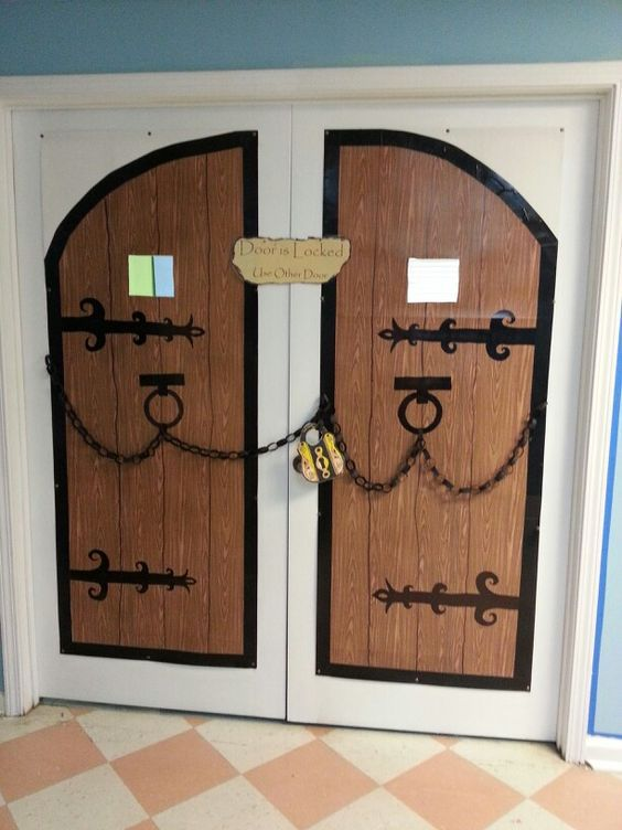 For castle theme classroom - castle doors are made from poster board covered with wood grain Contact Paper and black duct tape. The hinges are drawn on with permanent markers. And then I added paper chains and a lock because these doors are locked.: