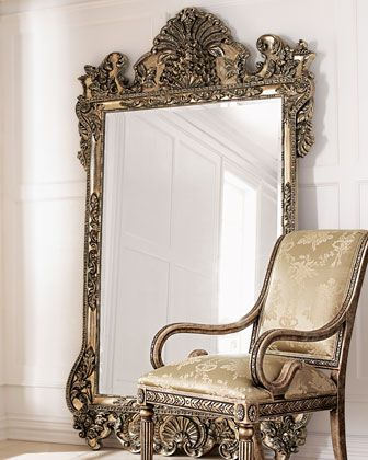 Mirror stands 7' tall. Frame is handcrafted of wood composite and resin with an antiqued metallic finish that varies from patinated silver to gold. Due to the nature of handcrafting, no two mirrors ar