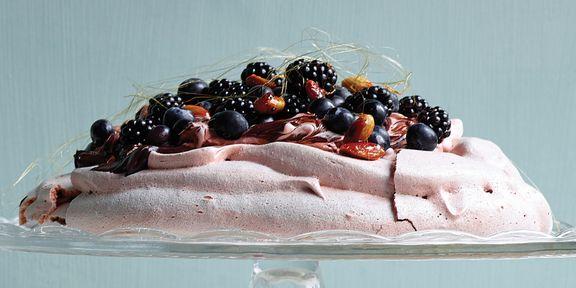 Pavlova met pure chocolade, gekarameliseerde amandelen, bramen en blauwe bosbessen