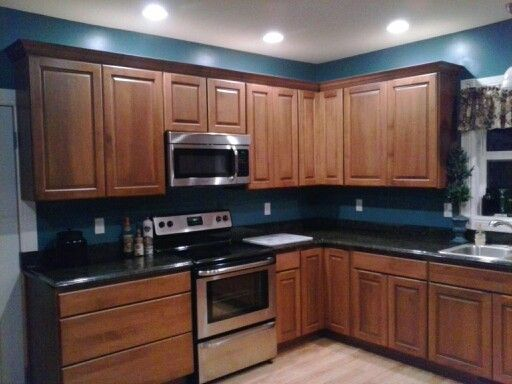 My kitchen remodel dark granite cherry cabinets teal for Dark blue kitchen paint