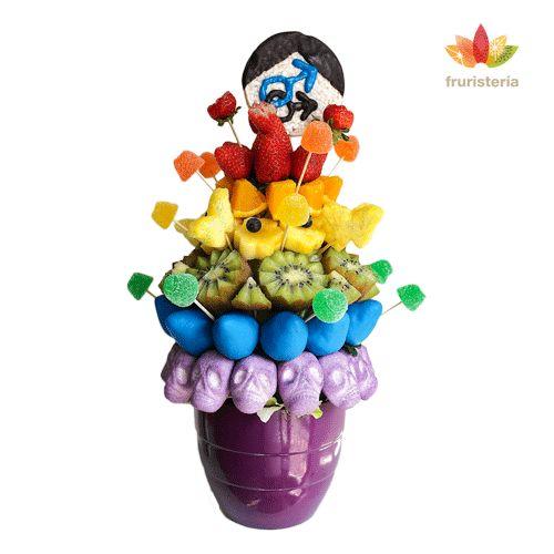 """Ramo """"Arcoiris""""   Sumérgete en un arcoiris de sabores deslumbrantes formado por dulces fresas, algunas cubiertas de chocolate azul, jugosas naranjas, flores de piña con arándanos, kiwis, nubes rellenas de chocolate y gominolas que saltan alrededor de las frutas. Incluye purpurina comestible para darle más brillo. Puedes elegir el símbolo que prefieras para la piruleta de arroz inflado (femenino o masculino)   @Fruristería"""