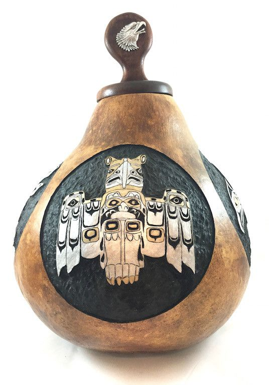 """Hand Carved Gourd featuring Northwestern Thunder Birds. Each bird is unique. Gourd is hollowed and accented with Gold and Silver paint and varnish. Gourd measures 14"""" high and 10"""" wide at the widest p"""