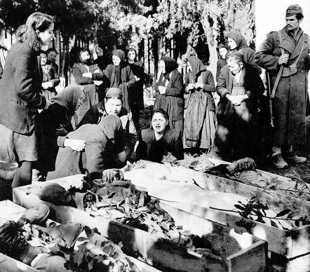 Greek women mourning the loss of their men and boys murdered by Communist guerrillas who came through their Macedonian town .1947