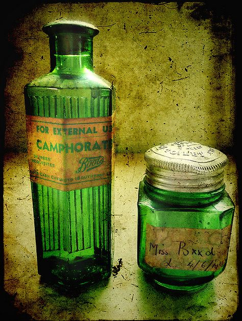 Old green glass bottles... need red berries and white flowers.