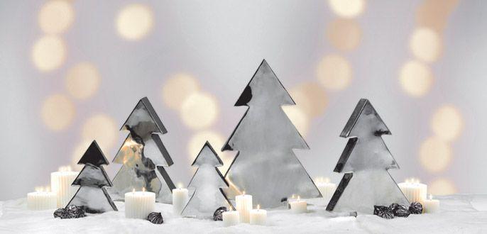 CREA L'ATMOSFERA GIUSTA Alberi in metallo in varie misure, candele bianche profumate, addobbi pendenti in vetro sfaccettati effetto argento.