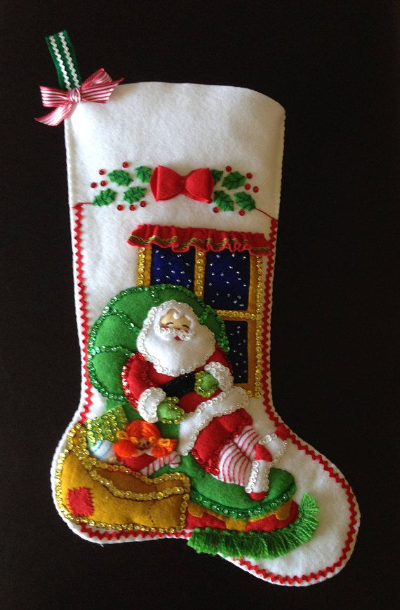 Santa Snoozing Jeweled felt stocking made with a Bucilla kit. This stocking is 18 inches in length, completely lined with nice quality white cotton fabric. I line the stockings so that you will have a Heirloom for many years. The lining helps give it shape and stability for ever lasting years, and if you want to put goodies in it at Christmas. I also have added more stability to the hanger. This stocking has many many beautiful hand sewn beads and sequins, and hand cut and trimmed pieces of…