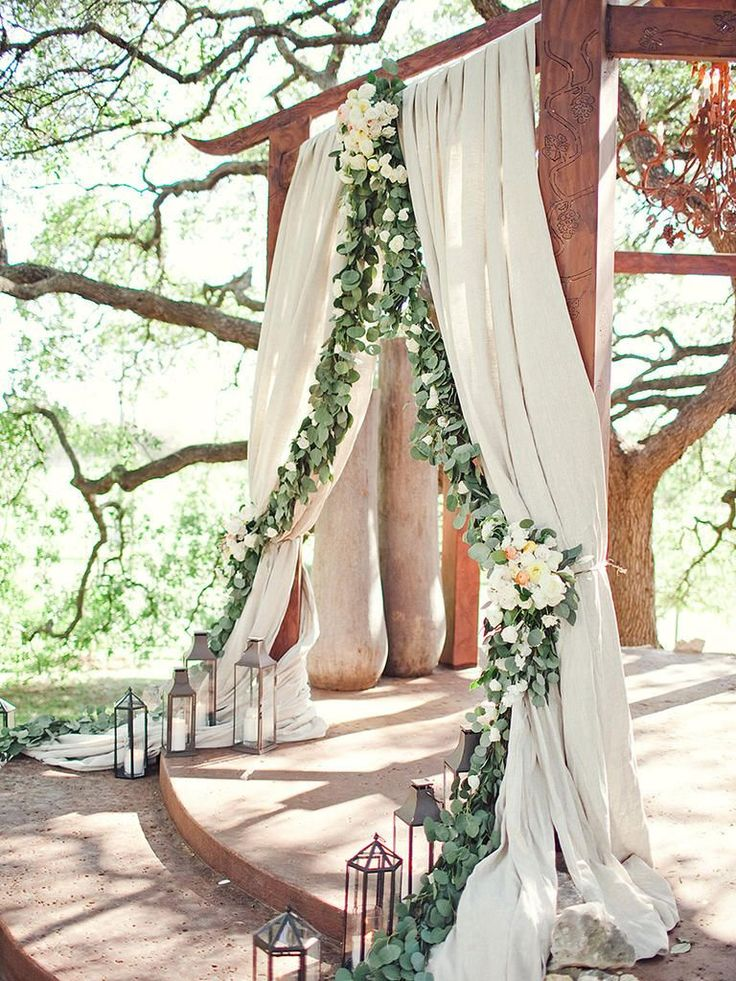 Softly drape an arbor with neutral-toned fabric and lush garland greenery for an alternative wedding ceremony altar that is natural yet refined.
