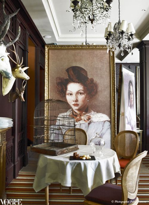 Oversized facsimiled portraits by impressionist painter Jean-Baptiste-Camille Corot, along with an old birdcage and antique wooden trophy heads, lend the gourmet restaurant within Les Etangs de Corot, a hotel near Paris, a quirky charm.  From 'Joie de Vivre', a story within Vogue Living July/Aug 2011.   Photo by Pablo Zamora.
