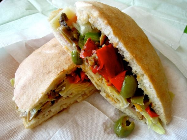 """la puccia: """"Lecce's answer to the sandwich is a pita-like dough, served warm and exploding with both fresh and pickled vegetables, then garnished with a slice or two of prosciutto and cheese."""" [no recip]"""