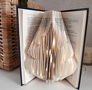 Kerstboom gevouwen uit boek met verlichting erin