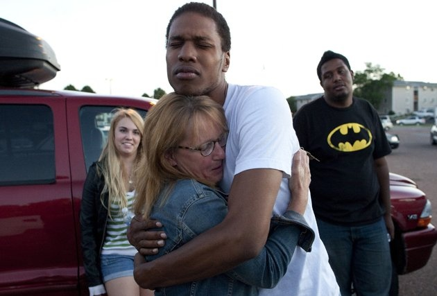 Judy Goos, center left, hugs her daughter's friend, Isaiah Bow, 20, while eyewitnesses Emma Goos, 19, left, and Terrell Wallin, 20, right, gather outside Gateway High School where witnesses were broug