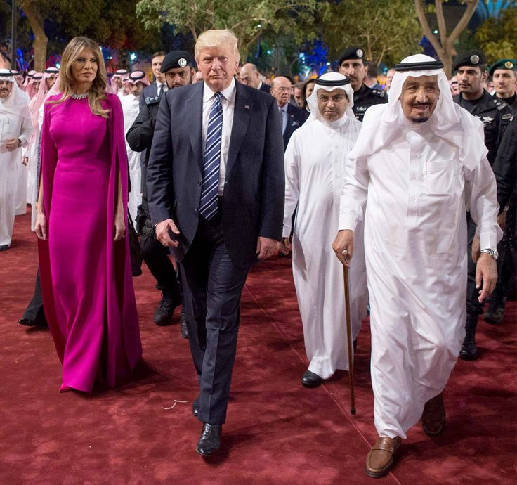 Melania Trump wears a fuschia cape-style floor-length dress with matching patent leather pumps at Murabba Palace in Saudi Arabia, escorted by King Salman for a great tour.